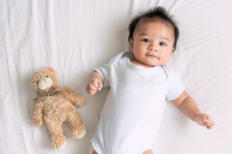 Портрет вползая младенца на кровати в ее комнате, прелестный ребенок в белой солнечной спальне, новорожденный ребенок ослабляя в  стоковая фотография rf