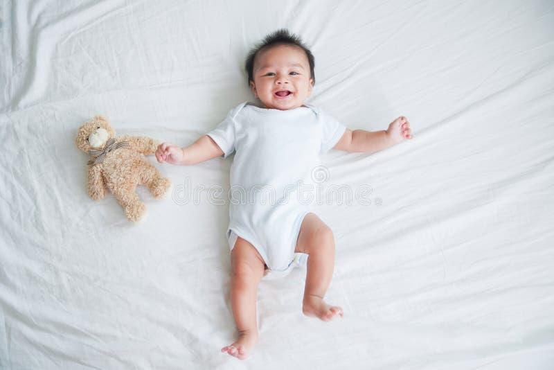 Портрет вползая младенца на кровати в ее комнате, прелестный ребёнок в белой солнечной спальне, новорожденный ребенок ослабляя в  стоковая фотография rf