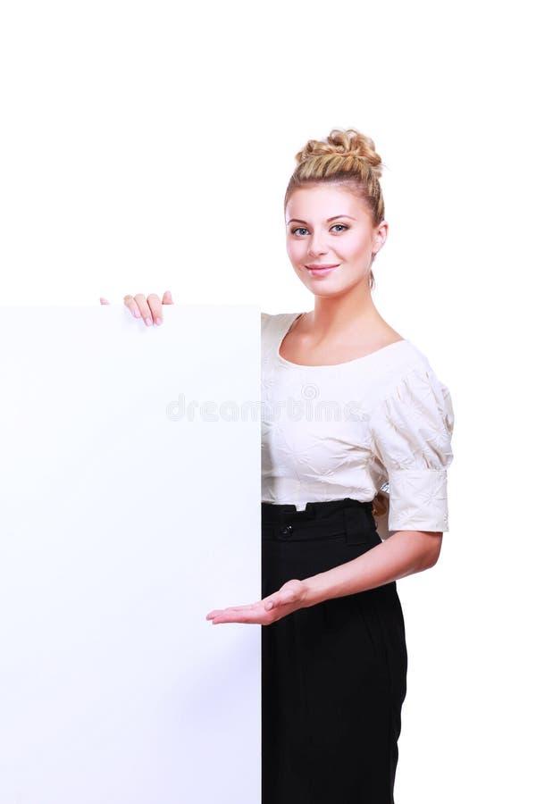 Портрет вскользь молодой женщины стоя около пустой карточки - над белой предпосылкой стоковое фото rf