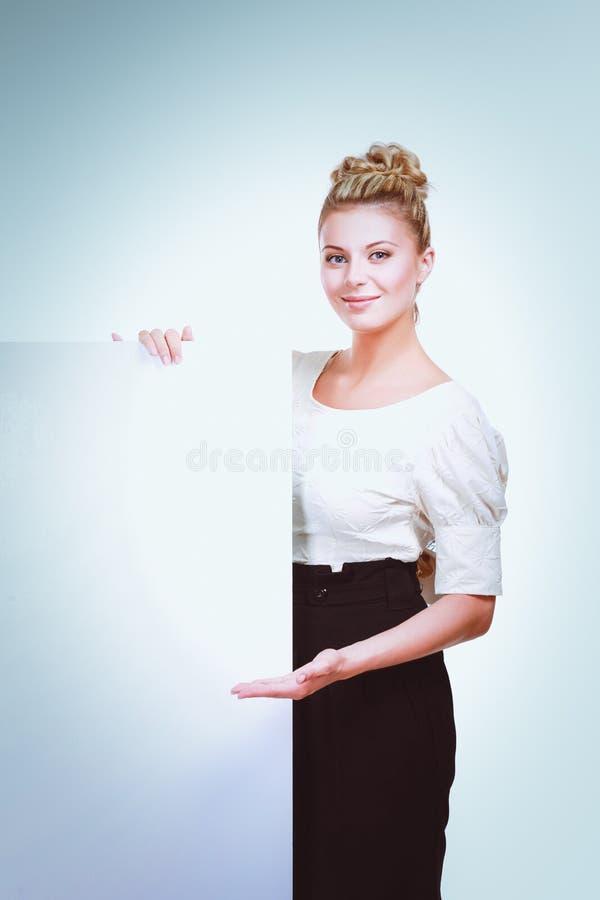 Портрет вскользь молодой женщины стоя около пустой карточки - над белой предпосылкой стоковое фото
