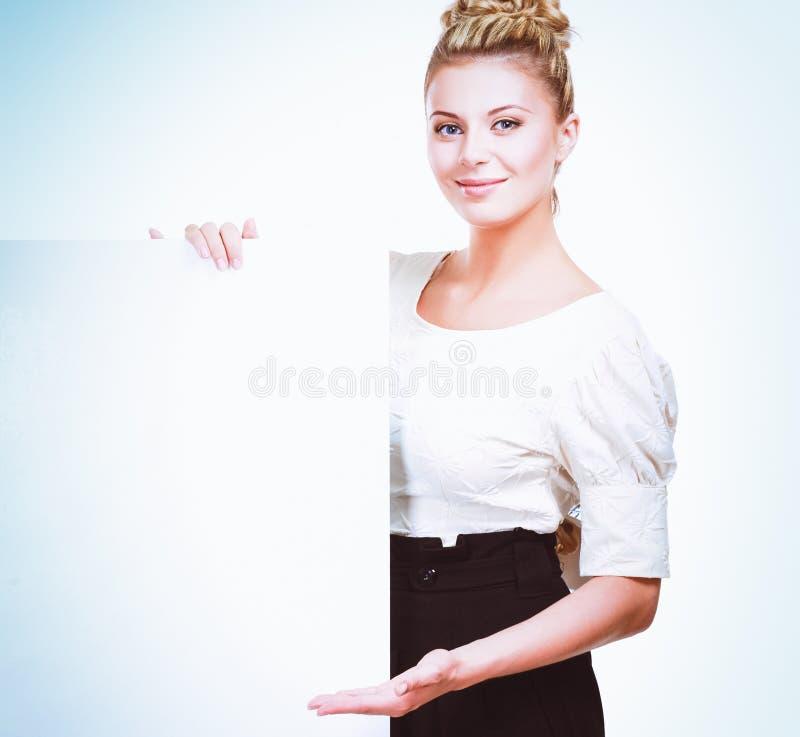 Портрет вскользь молодой женщины стоя около пустой карточки - над белой предпосылкой стоковые изображения