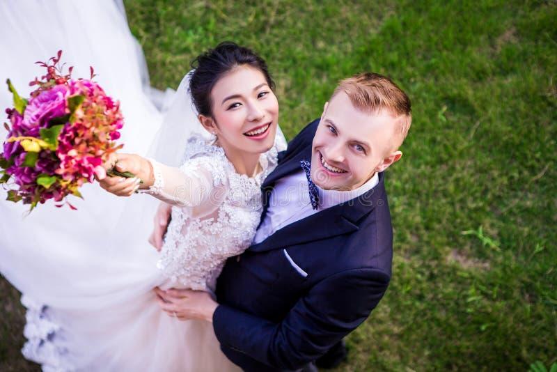 Портрет высокого угла жизнерадостных пар свадьбы стоя на травянистом поле стоковые фотографии rf