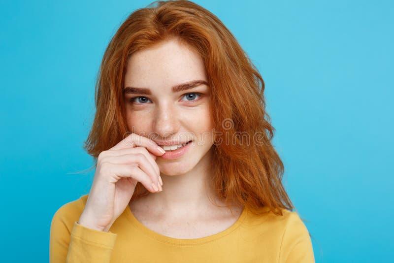 Портрет выстрела в голову девушки волос счастливого имбиря красной с веснушками усмехаясь смотрящ камеру Пастельная голубая предп стоковые изображения