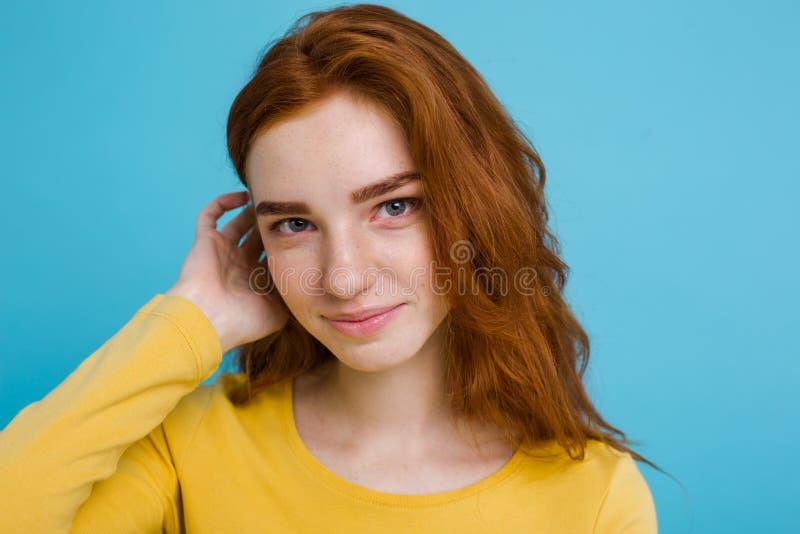 Портрет выстрела в голову девушки волос счастливого имбиря красной с веснушками усмехаясь смотрящ камеру Пастельная голубая предп стоковое изображение rf