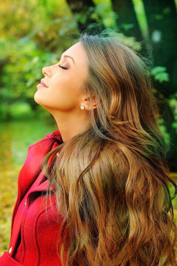 Портрет в профиле молодой красивой девушки отдыхая в парке стоковое изображение