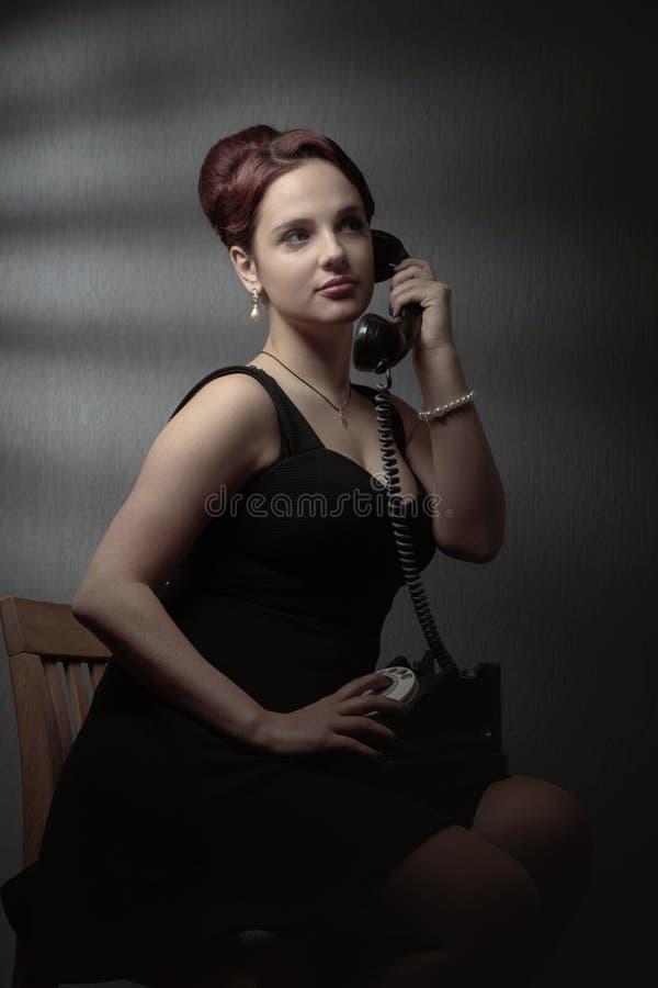 Портрет в ретро стиле со старым черным телефоном стоковое фото