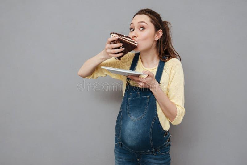Портрет голодной беременной женщины есть сладостный шоколадный торт стоковое изображение rf