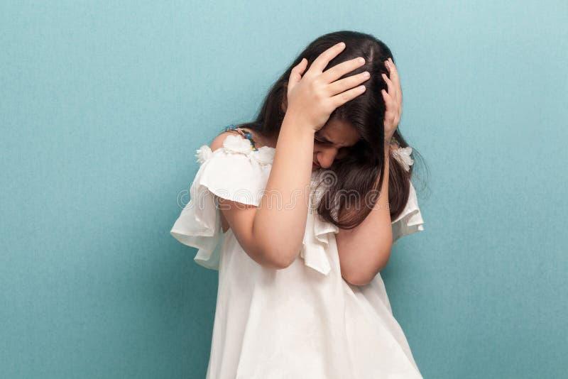 Портрет грустной красивой маленькой девочки брюнета с черными длинными прямыми волосами в белом положении платья держа ее голову  стоковое фото