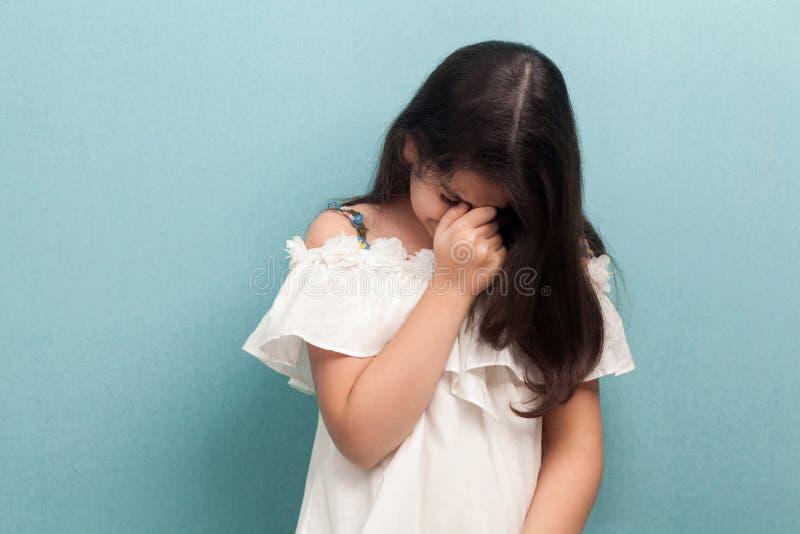 Портрет грустной несчастной красивой маленькой девочки брюнета с черными длинными прямыми волосами в белом платье стоя и плача стоковое изображение rf