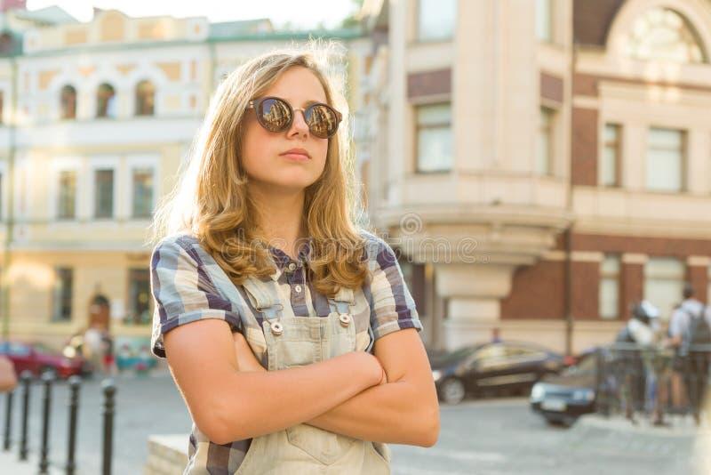 Портрет грустной несчастной предназначенной для подростков девушки со сложенными руками на улице города, космосе экземпляра стоковая фотография