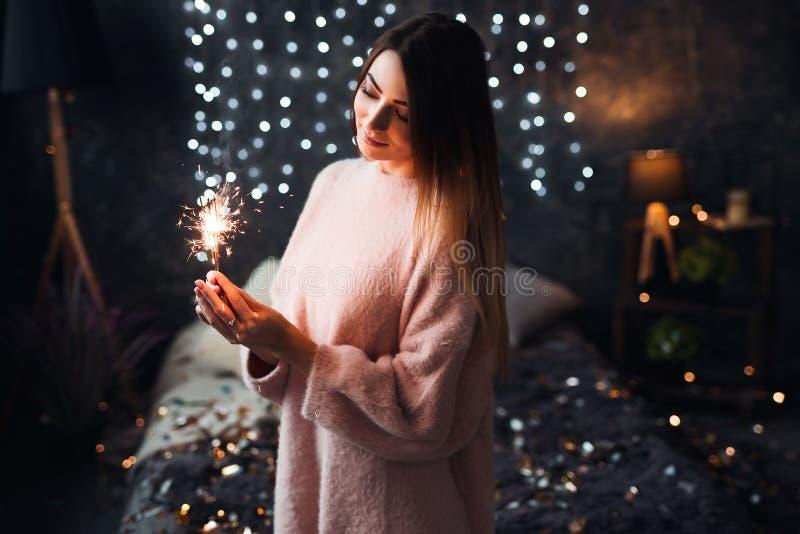 Портрет грустной привлекательной молодой женщины с колбасными конфетти и гарландовыми огнями, празднующими одиноко в темной комна стоковые изображения