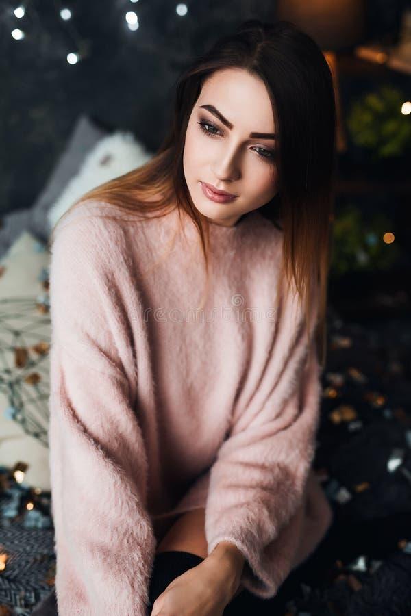 Портрет грустной привлекательной молодой женщины с колбасными конфетти и гарландовыми огнями, празднующими одиноко в темной комна стоковые фотографии rf