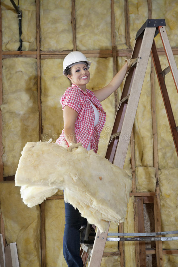 Портрет губки нося счастливого женского рабочий-строителя пока взбирающся лестница стоковые изображения