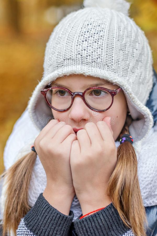 Портрет девочка-подростка в стеклах, дуя на ее руках для того чтобы держать теплый в холоде стоковые изображения rf