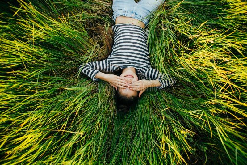 Портрет девочка-подростка лежа на траве и глазах покрывая ее глаза стоковое фото