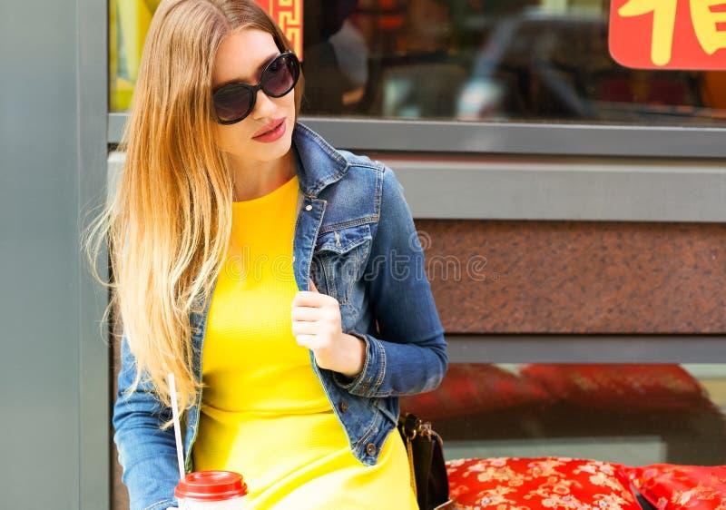 Портрет Девушка в солнечных очках, красивом желтом платье лета и куртке джинсовой ткани сидит в азиатском кафе на теплом вечере л стоковое фото rf