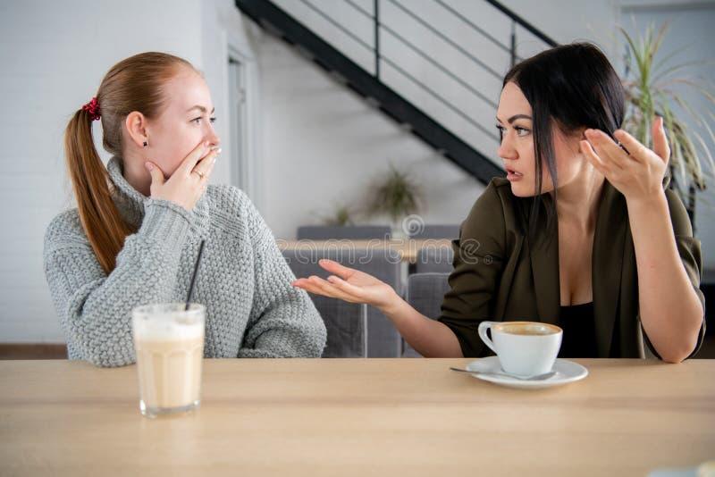 Портрет девушки говоря секреты к ее изумленному другу сидя на кафе во время перерыва на ланч стоковое фото