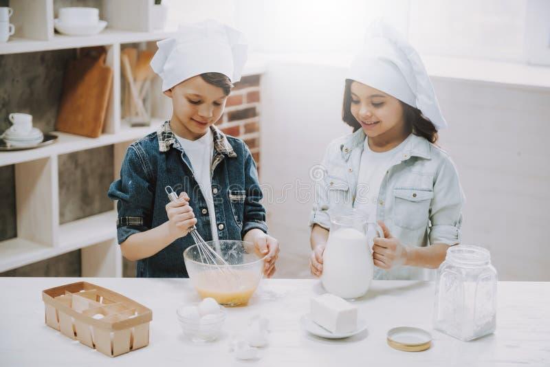 Портрет девушки и мальчика варя на кухне стоковое изображение