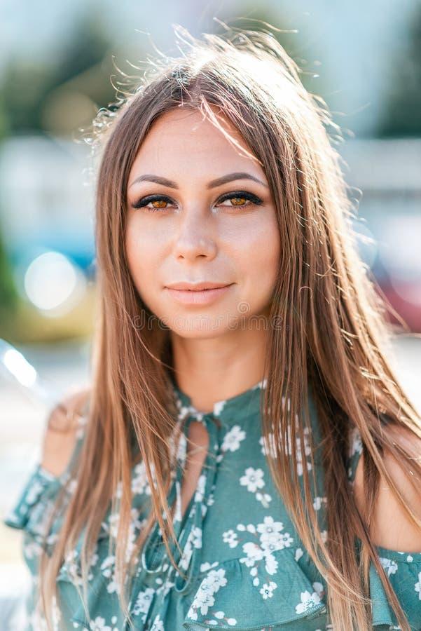 Портрет девушки летом в городе Конец-вверх, длинные волосы, зеленая блузка Случайный макияж Эмоции утехи, улыбки  стоковое фото
