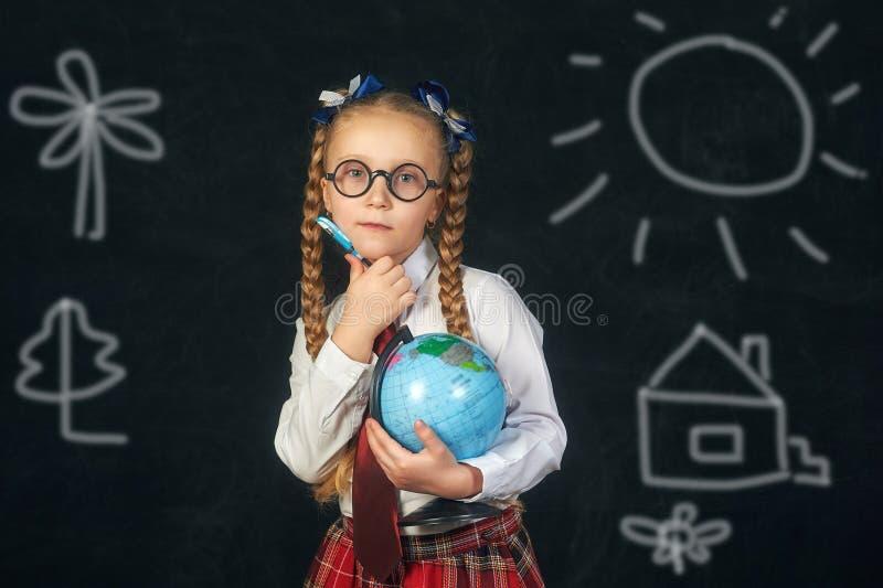 Портрет девушки начальной школы с глобусом Школьная форма стоковое изображение