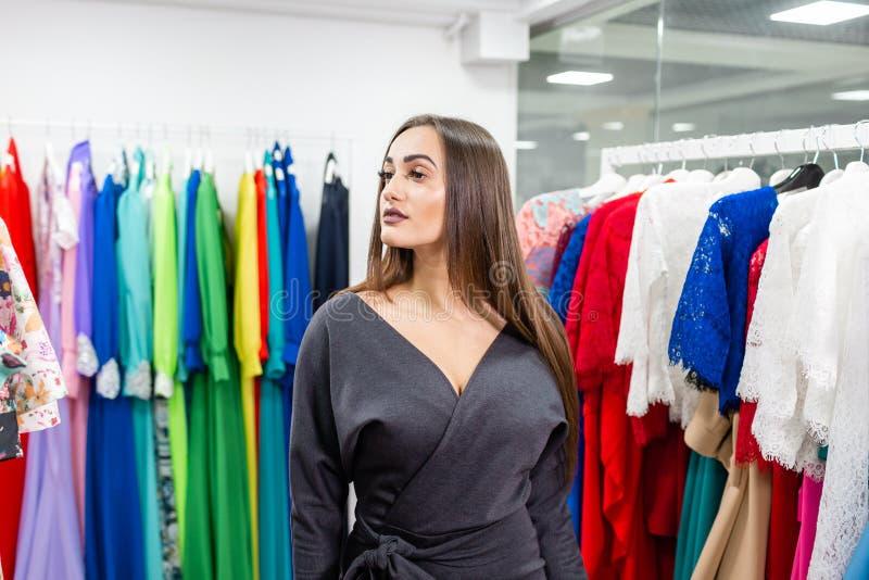 Портрет девушки на предпосылке одежд на вешалках в магазине одежды Счастливая молодая женщина выбирая одежды стоковая фотография rf