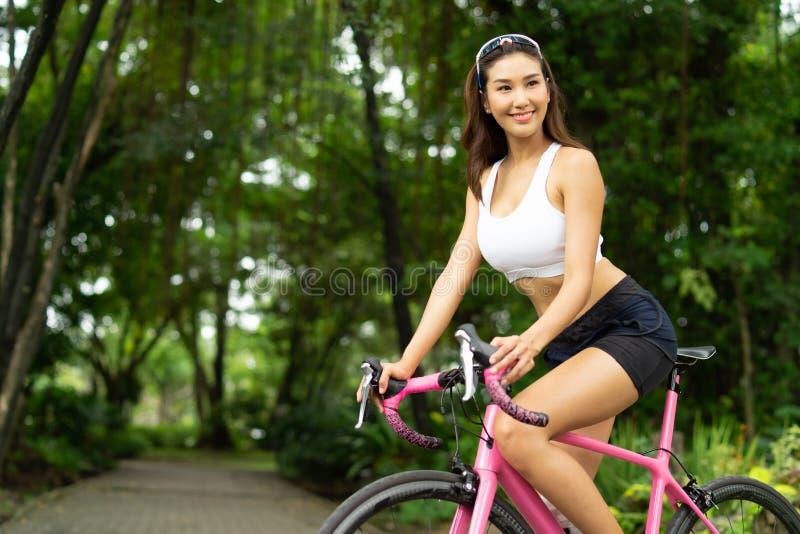 Портрет девушки спорта smiley красивой ехать розовый велосипед в парке стоковая фотография rf