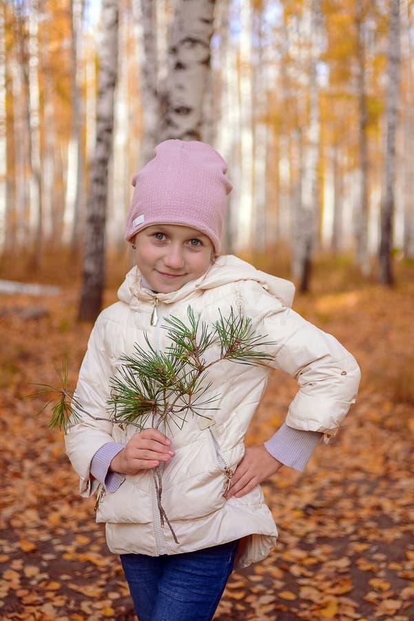 Портрет девушки с голубыми глазами которой стоит в девушке подростка леса осени в шляпе и куртке против предпосылки  стоковое фото rf
