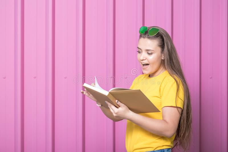 Портрет девушки с книгой против розовой предпосылки стены металла записывает старую принципиальной схемы изолированная образовани стоковые изображения
