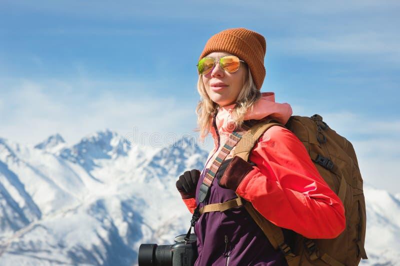 Портрет девушки хипстера фотографа туристской с камерой в солнечных очках и шляпе на фоне снега стоковое фото