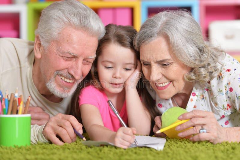Портрет дедов играя с их grandaughter пока лежащ на поле стоковое фото rf