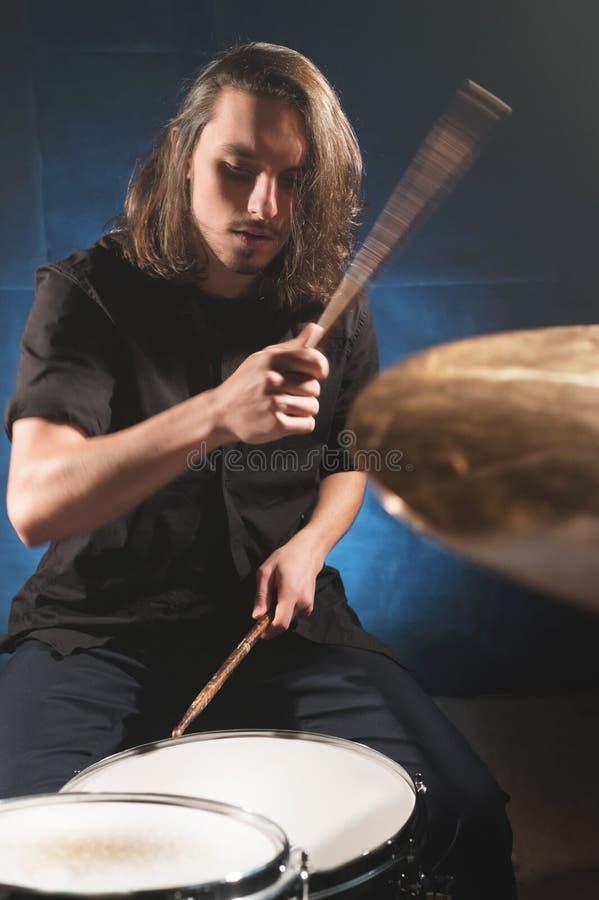 Портрет длинн-с волосами барабанщика с палочками в его руках сидя за набором барабанчика Низкий ключ Концепции  стоковая фотография rf