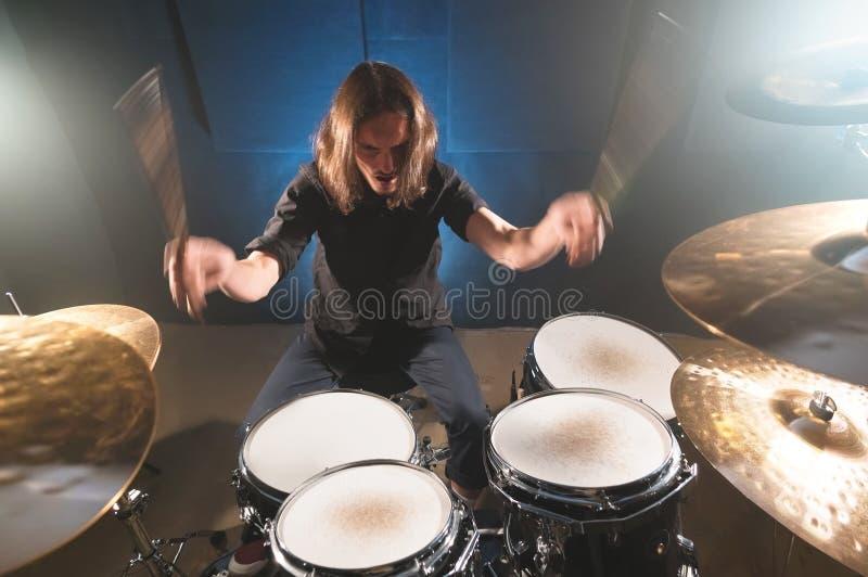 Портрет длинн-с волосами барабанщика с палочками в его руках сидя за набором барабанчика Низкий ключ Концепции  стоковая фотография
