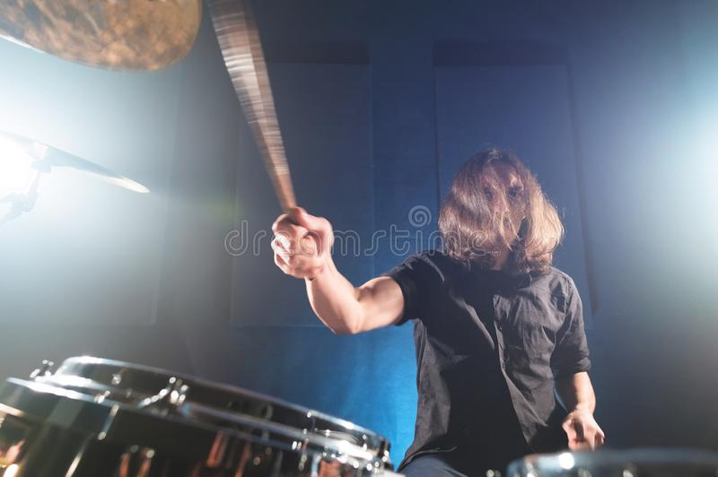 Портрет длинн-с волосами барабанщика с палочками в его руках сидя за набором барабанчика Низкий ключ Концепции  стоковое фото rf