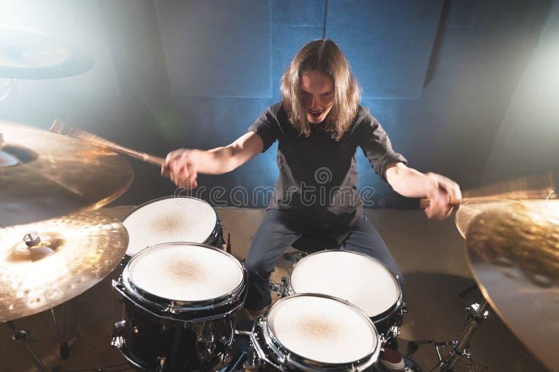 Портрет длинн-с волосами барабанщика с палочками в его руках сидя за набором барабанчика Низкий ключ Концепции  стоковое изображение rf