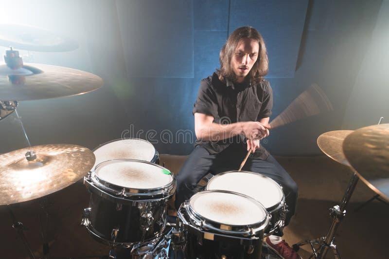 Портрет длинн-с волосами барабанщика с палочками в его руках сидя за набором барабанчика Низкий ключ Концепции  стоковое изображение