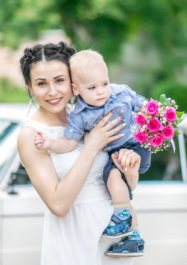 Портрет довольно молодой женской невесты идя, держа ребёнок с букетом роз свадьбы и смотря в камеру на солнечном лете стоковая фотография rf