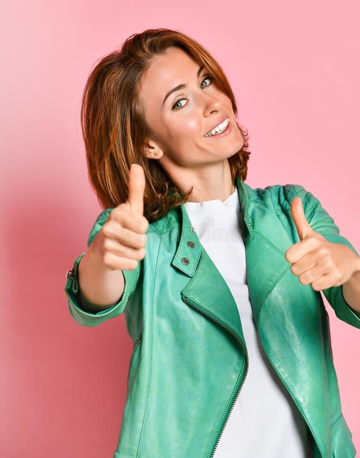 Портрет довольно привлекательной женщины в зеленой кожаной куртке, показывая большие пальцы руки вверх с 2 руками на розовой пред стоковое фото rf
