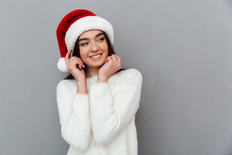 Портрет довольно симпатичной девушки нося красную шляпу santa стоковое изображение