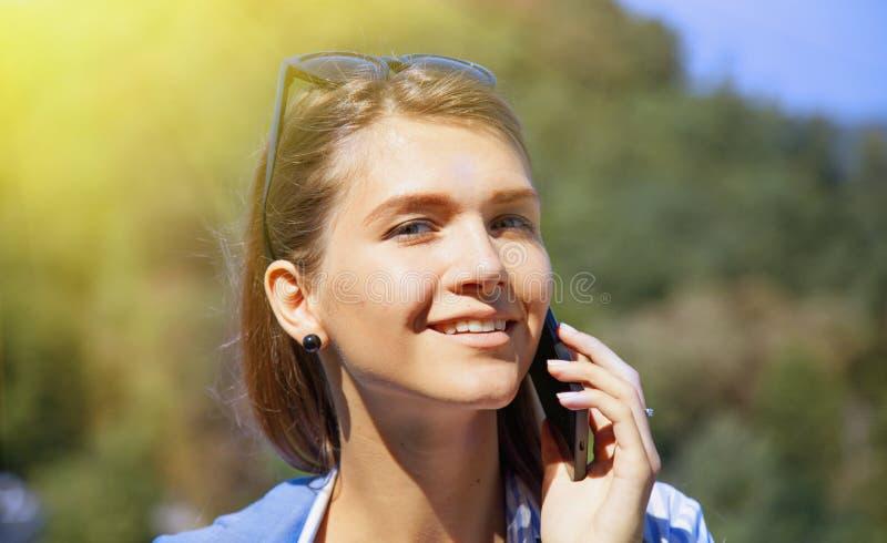 Портрет довольно счастливой симпатичной молодой женщины говоря на передвижном p стоковая фотография rf
