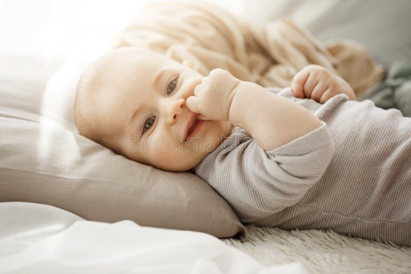 Портрет дочери помадки усмехаясь newborn лежа на уютной кровати Ребенок смотрит камеру и касающую сторону с ее маленьким стоковая фотография