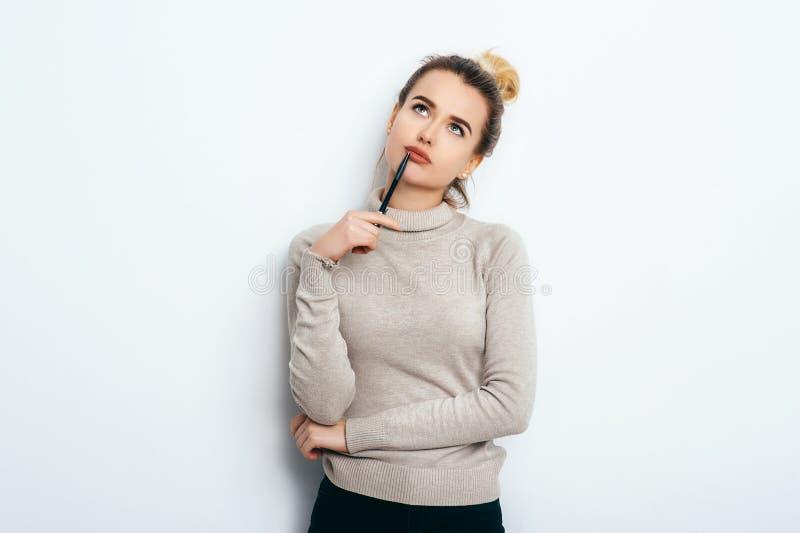 Портрет думая женщины с умоляющей улыбкой, имеющ плюшку волос в свитере изолированном на белой ручке удерживания предпосылки и им стоковые фотографии rf