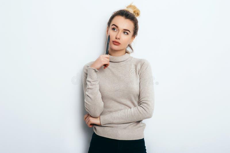 Портрет думая женщины с умоляющей улыбкой, имеющ плюшку волос в свитере изолированном на белой ручке удерживания предпосылки и им стоковая фотография