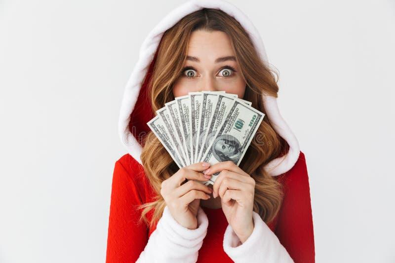 Портрет европейской женщины 20s нося костюм Санта Клауса красный усмехаясь и держа вентилятор денег в банкнотах доллара, изолиров стоковое изображение rf