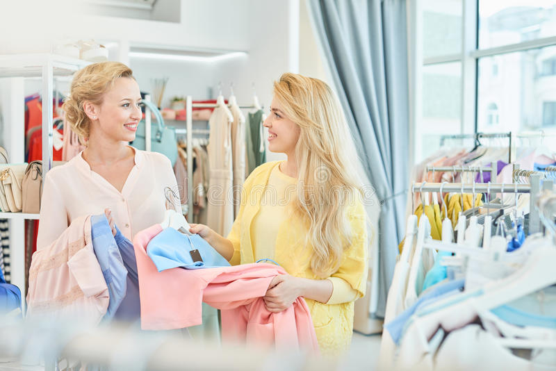 Портрет 2 девушек в магазине одежды стоковые изображения
