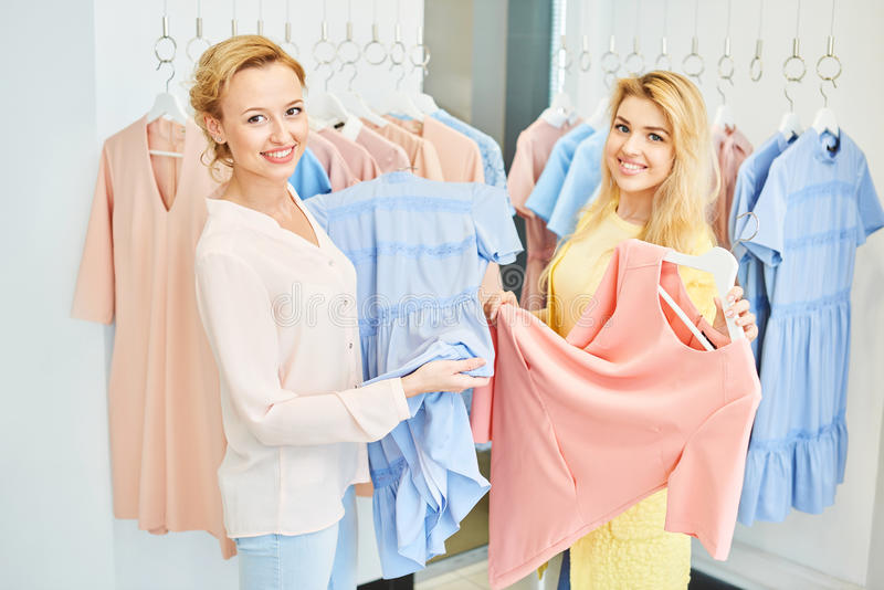 Портрет 2 девушек в магазине одежды стоковое фото