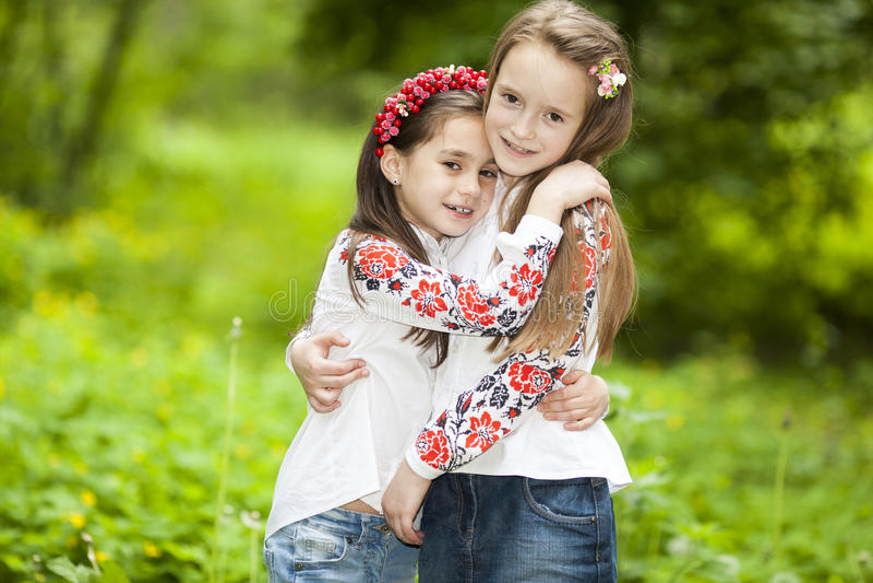 Портрет 2 девушек в парке на предпосылке зеленого дерева стоковые фотографии rf
