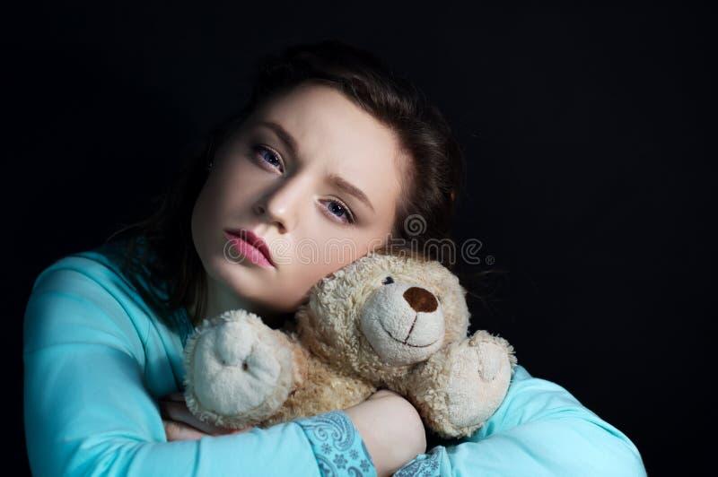 Портрет девушки в темноте с медведем стоковое изображение