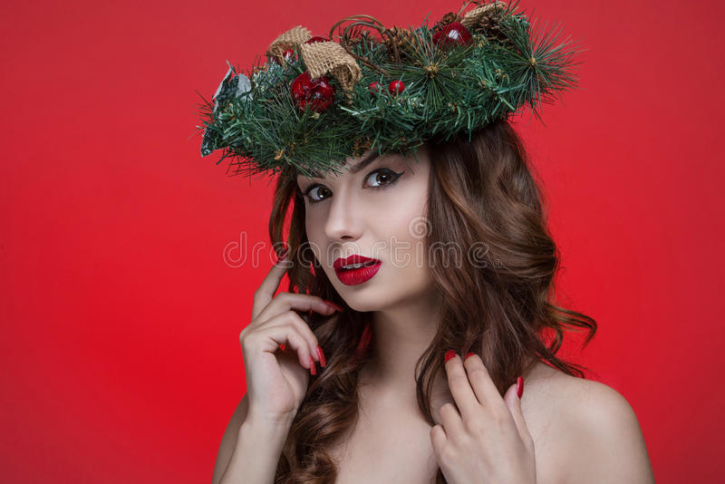 Портрет девушки красоты рождества или Нового Года изолированный на красной предпосылке Красивая женщина с роскошным венком состав стоковое изображение rf