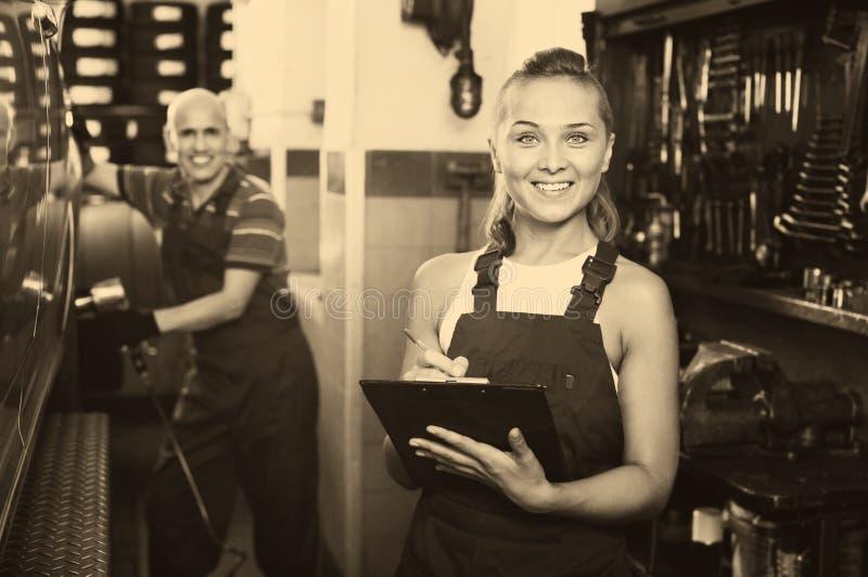 Портрет девушки механика в coveralls имея картон с doc стоковая фотография