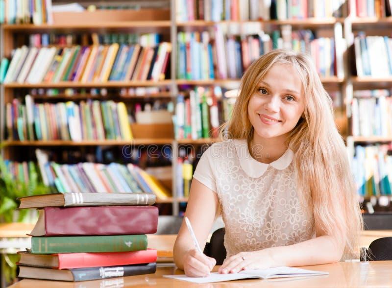 Портрет девушки студента изучая на библиотеке стоковое фото